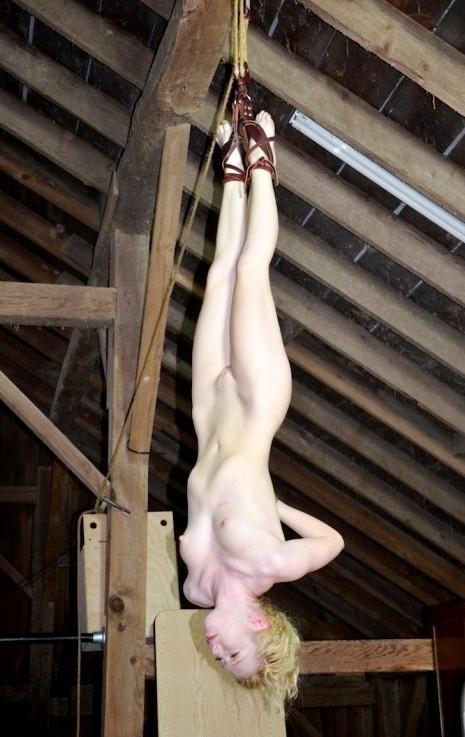 Big boobed nude women hung upside down