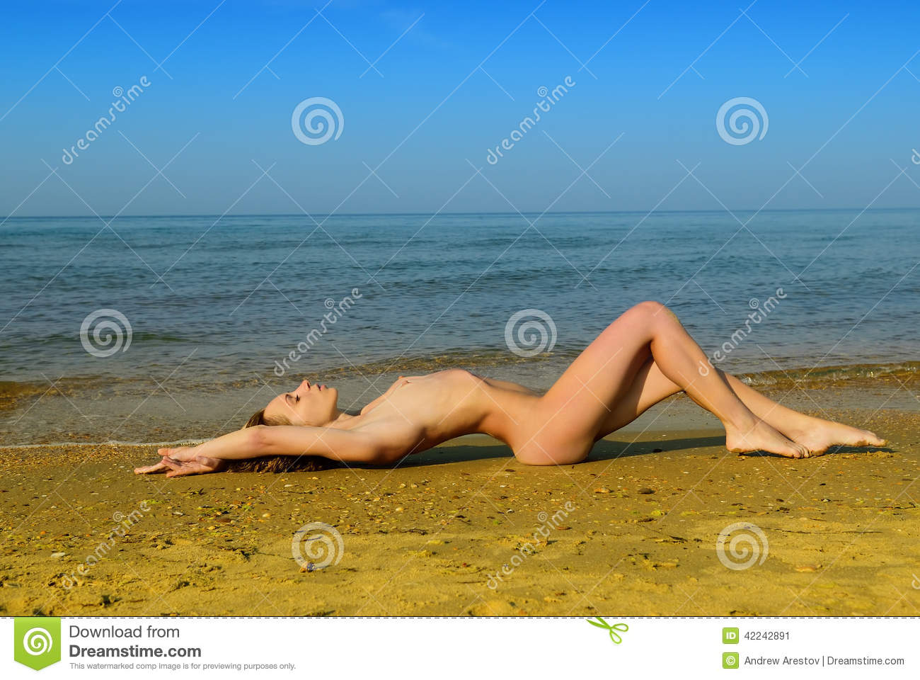 Nude girls laying down on the beach
